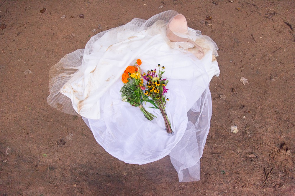 trashed wedding dress and bouquet in the mud