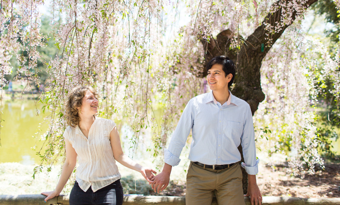 Brooklyn Botanical Garden Engagement Photos Sarah and Albert holding hands in front of a white Cherry Blossom Tree