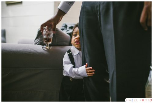 2 year old Boy hugging his father's leg at cape cod wedding. Documentary wedding photography