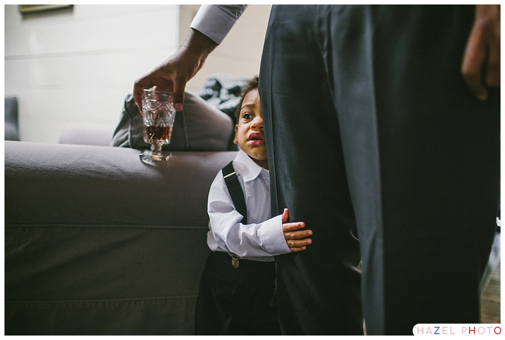 Boy in suit and suspenders hugging his daddy's leg at a wedding. Documentary Wedding Photography