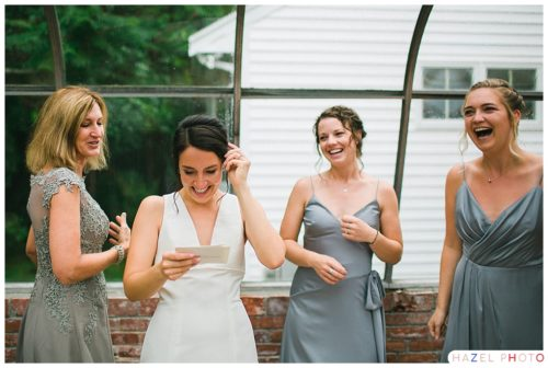 Bride reading a letter from her groom and crying surrounded by bridesmaids at a Thompson Inn Wedding. Documentary wedding photography