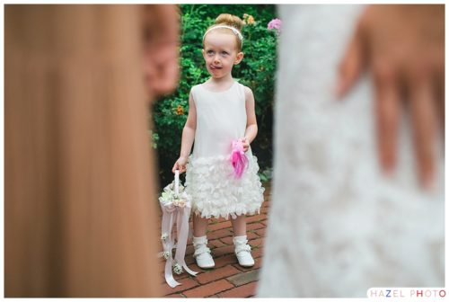 Flower girl in a white dress sticking her tongue out and observing it all at an Irish wedding. Documentary wedding photography