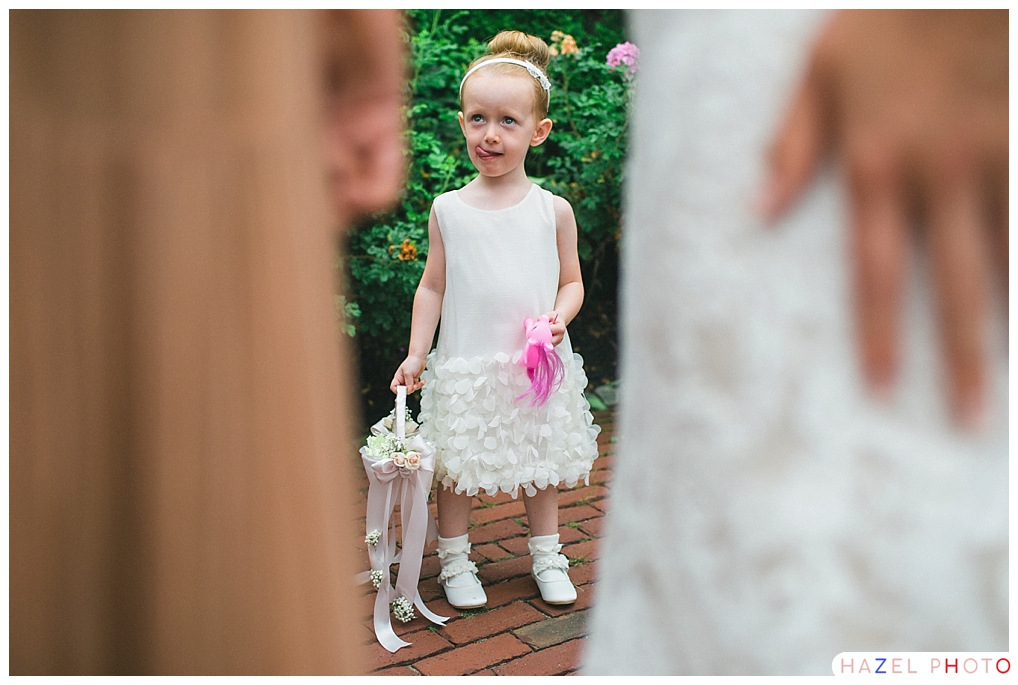 a little girl in a white dress with a white basket and a bright pink troll, sticking her tongue out and observing it all on a wedding day. Documentary wedding photography.