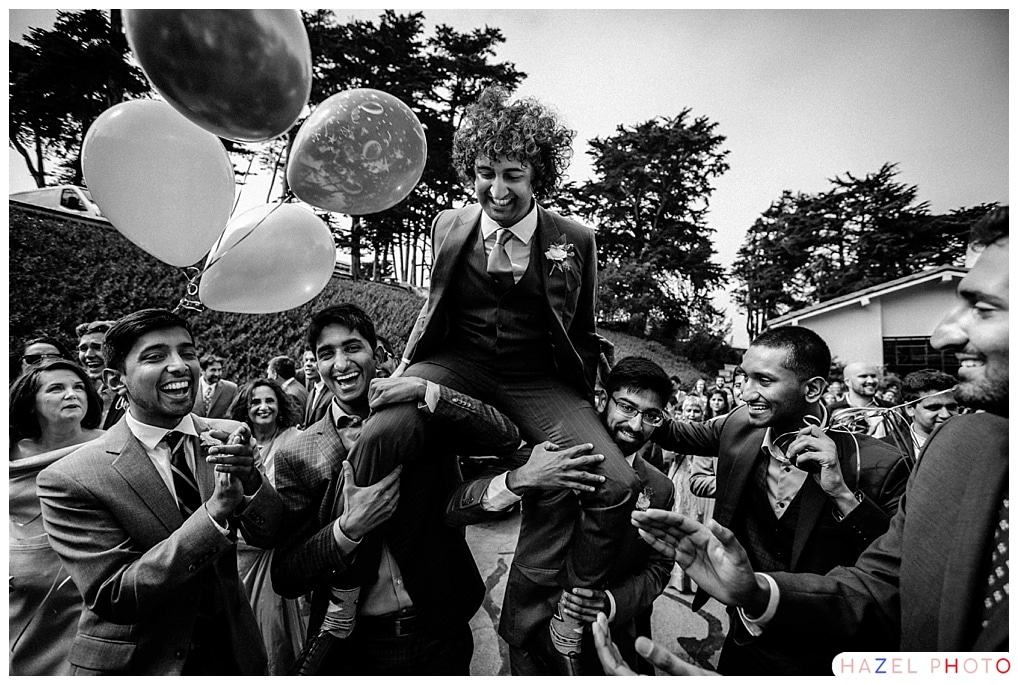 A groom held aloft his cousins' shoulders during a baraat. Documentary Wedding Photography Hazel Photo