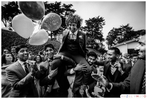 Groom held aloft on his cousins' shoulders during a baraat at a Golden Gate Club Wedding. Documentary wedding photography