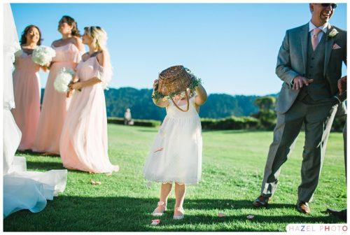 Flower girl dumping out floors in a field at a Crystal Springs Golf wedding Documentary wedding photography
